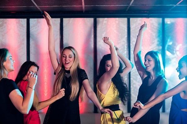 Smiling friends dancing on dance floor in bar